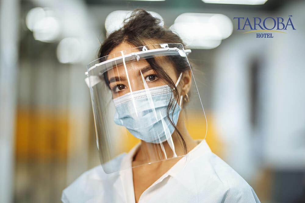 Mulher usando face shield para viajar de avião na pandemia