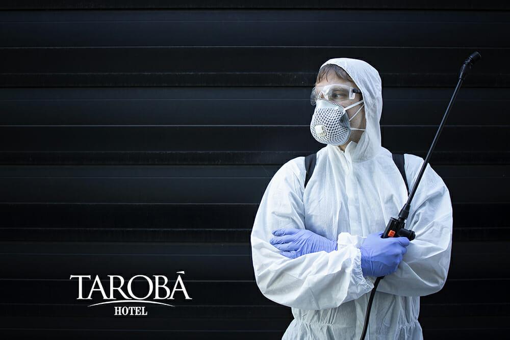 Homem segurando um pulverizador eletrostático para limpar o ambiente do avião